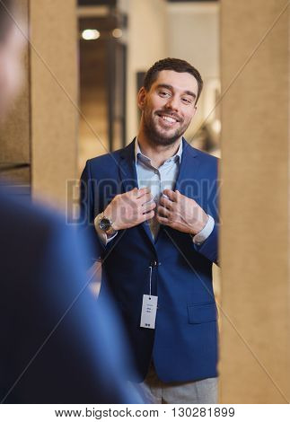 sale, shopping, fashion, style and people concept - happy young man choosing and trying jacket on and looking to mirror in mall or clothing store