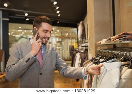 sale, shopping, fashion, communication and people concept - happy young man or businessman calling on smartphone and choosing clothes at clothing store