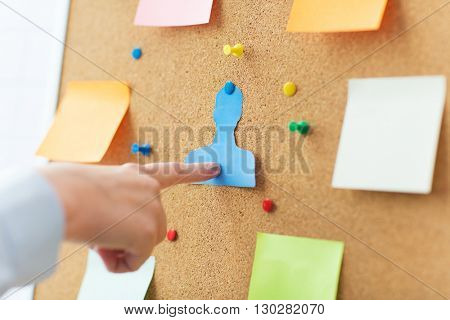business, people, employment, headhunting and hiring concept - close up of hand pointing to to human shape on cork board with stickers and office pins