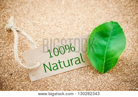 100% Natural word on recycle brown tag with green leaf on wooden background.