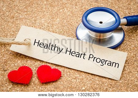 Healthy heart program word in paper tag with red heart and stethoscope on wood table. Medical concept.