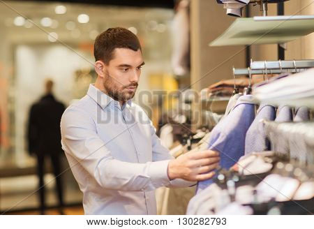 sale, shopping, fashion, style and people concept - elegant young man in shirt choosing clothes in mall or clothing store