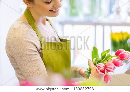 people, business, sale and floristry concept - close up of happy florist woman making tulip bunch at flower shop