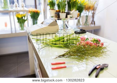 people, business, sale and floristry concept - close up of floristic tools on flower shop counter