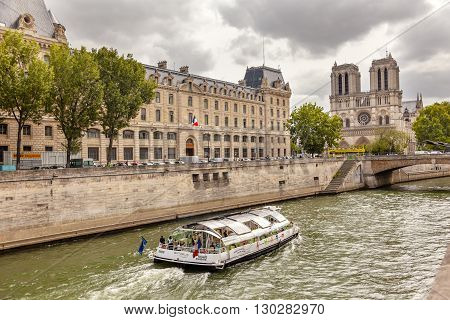 PARIS, FRANCE - JUNE 1, 2015 Tour Boat Seine River Notre Dame Spires Towers Bridge Overcast Skies Notre Dame Cathedral Paris France. Notre Dame was built between 1163 and 1250 AD.