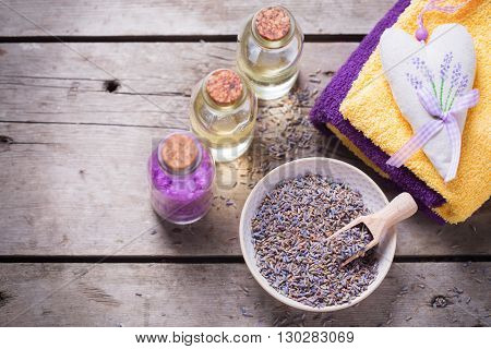 Lavander spa setting. Natural organic cosmetics. Sea salt bottles with oil and towels on vintage wooden background. Selective focus.