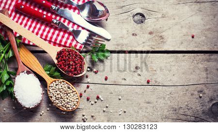 Seasoning for cooking. Red and white pepper and sea salt in wooden spoon on aged wooden background. Food ingredient. Selective focus. Place for text. Flat lay. Top view.