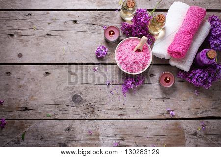 Spa setting. Sea salt candles aroma oil in bottles and towels on vintage wooden background. Selective focus. Flat lay. Place for text.