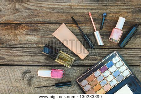 Cosmetics: mascara, eyeliner, false eyelashes, concealer, nail polish, perfume, lip gloss and eye shadow on wooden background. Toned image.a