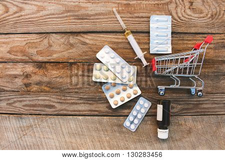 Shopping cart with pills, syringe, candles on old wood background. Toned image.