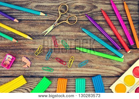 Stationery objects. School supplies on old wood background. Toned image.