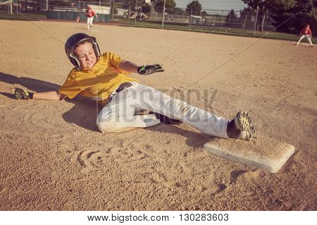 Youth Baseball playing sliding to second base.