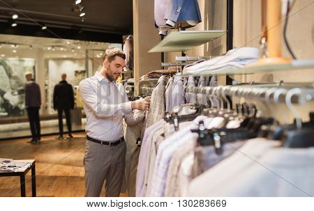 sale, shopping, fashion, style and people concept - elegant young man choosing clothes in mall or clothing store