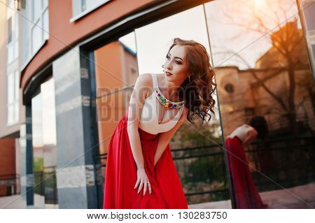 Portrait Of Fashionable Girl At Red Evening Dress With Open Bust Posed Background Mirror Window Of M