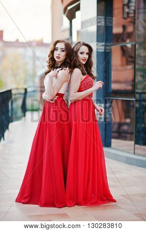 Portrait Of Two Fashionable Girls At Red Evening Dress Posed Background Mirror Window Of Modern Buil