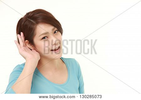 portrait of young woman with hand behind ear listening closely on white background