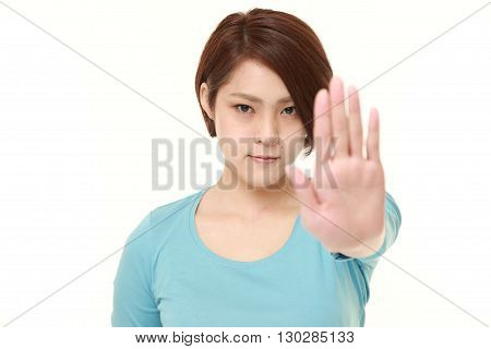 portrait of young Japanese woman making stop gesture on white background