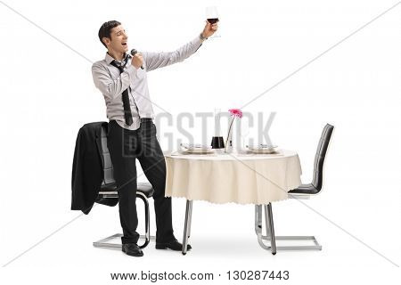 Drunk young man holding a glass of wine in a restaurant and singing on a microphone isolated on white background