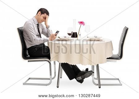 Disappointed young man reading a cancelation text message from his date isolated on white background