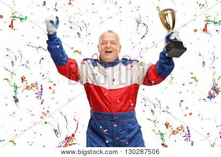 Delighted mature car racing champion holding a trophy and celebrating with confetti streamers around him