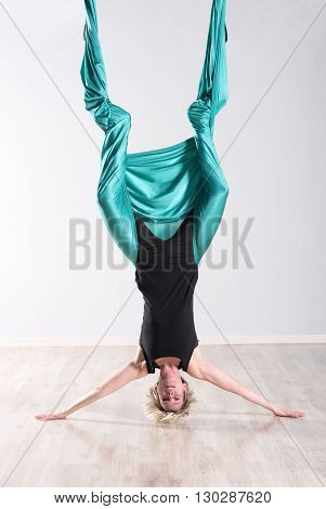 Woman Doing Aerial Yoga Upside Down On Head