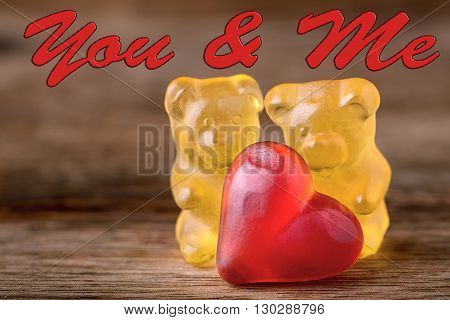 macro two yellow gummy bears with red hearts and you & me written on wood