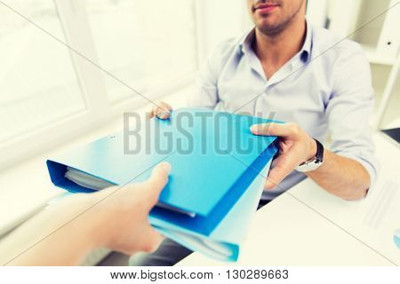 business, people and paperwork concept - close up of businessman taking folders with papers from secretary hand in office