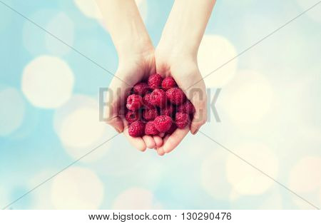 healthy eating, dieting, vegetarian food and people concept - close up of woman hands holding ripe raspberries over blue lights background