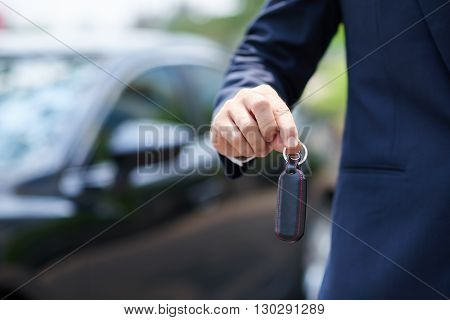 Close-up image of man giving you keys of his car