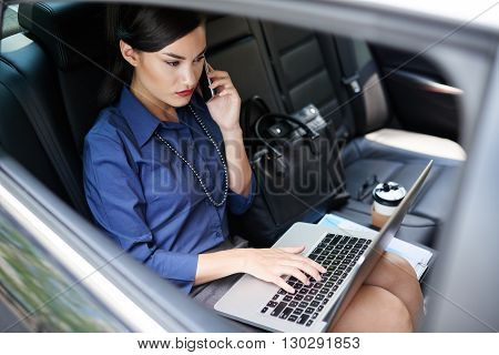 Elegant business lady sitting in car and working on laptop