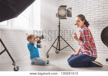 Photographer in motion. Young woman photographer and child girl having fun at the photo session.