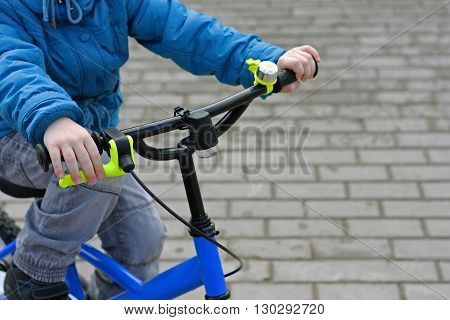 The image of the child who is riding a children's Bicycle. Side view. The child's hands to control the Bicycle handlebar.