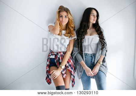 Two young beautiful girls laughing and posing on wall background. Fresh style life style.