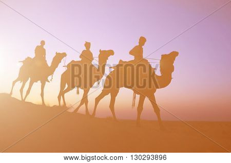 Three indigenous men riding camel through the dimly lit desert.