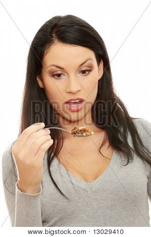 Young beautiful caucasian woman shocked while eating a cake -spoon bending - too much calories concept