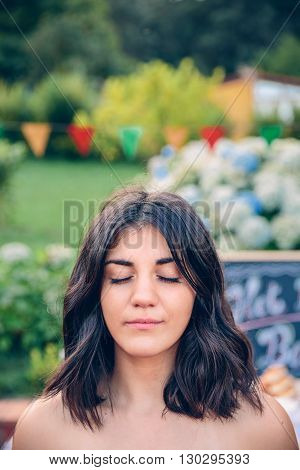 Portrait of black haired beautiful young woman with closed eyes against of garden in a outdoors summer party