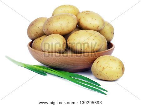 Raw unpeeled potatoes in a wooden bowl and green onions, isolated on white background.