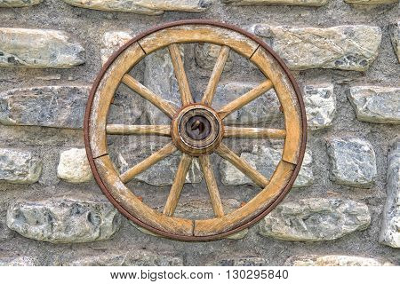Far West Wagon Wheel On Stone Wall