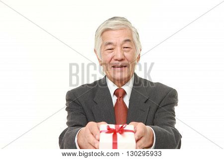 senior Japanese businessman offering a gift on white background