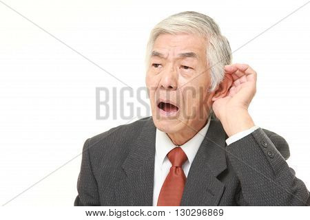 portrait of senior Japanese businessman with hand behind ear listening closely on white background