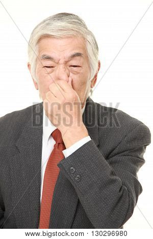 portrait of senior Japanese businessman holding his nose because of a bad smell on white background