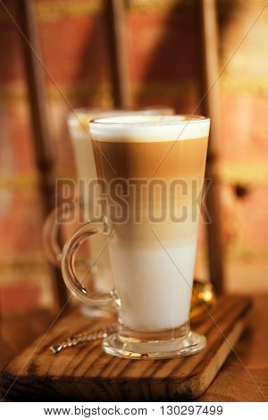 latte coffee in tall glasses on vintage chair with old brick wall, shallow dof