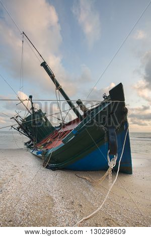 fishing boat at sunrise on beach with pier in far distance