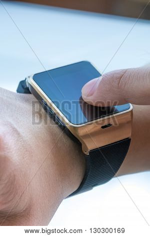 Close-up Of Man Using Smartwatch App With Finger