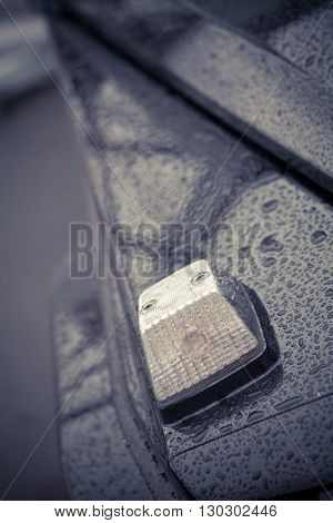 Close up shot of the turn signal of a car on a rainy day.