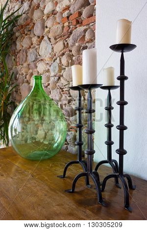 fragment of a room interior with a glass vase and with forged candlesticks a closeup and a stone wall