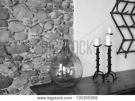 fragment of a room interior with a glass vase and with forged candlesticks a closeup and a stone wall of monochrome tone