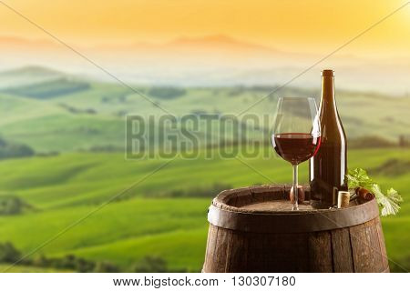 Red wine with wooden barrel on vineyard in Tuscany, Italy