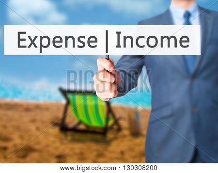 Income Expense - Businessman Hand Holding Sign