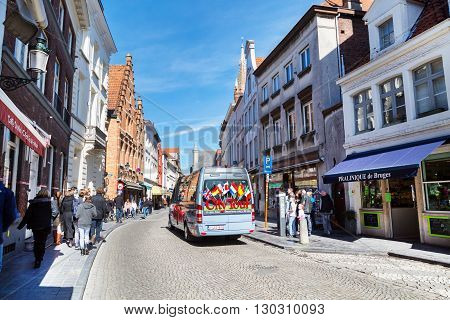 Bruges, Belgium - April 10, 2016: Colorful Hop on hop off Sightseeing Tours bus in Bruges street